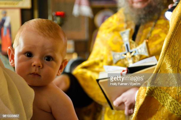 Close-Up Portrait Of Cute Baby By Priest In Church