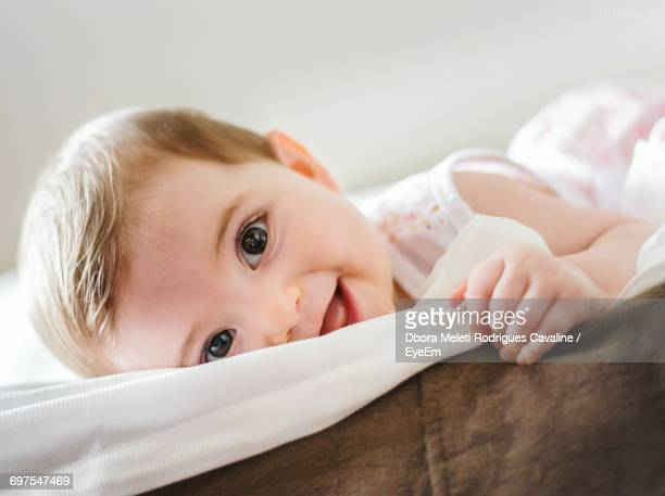 Close-Up Portrait Of Cute Baby Girl Lying On Bed At Home