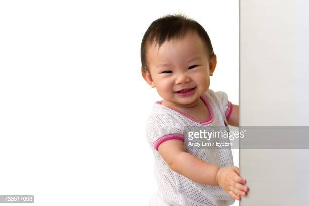 Close-Up Portrait Of Cute Baby Girl Standing By Wall Against White Background