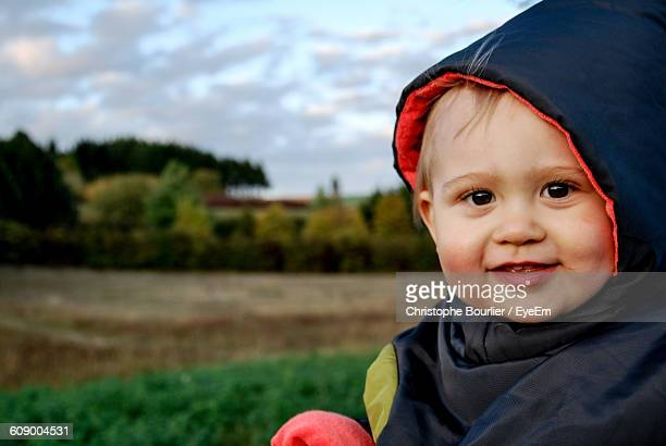 Close-Up Portrait Of Cute Baby Wearing Hooded Shirt At Field