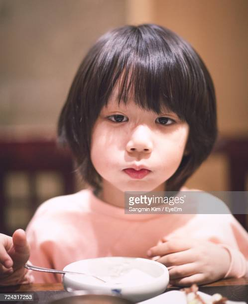 Close-Up Portrait Of Cute Boy Standing By Dining Table