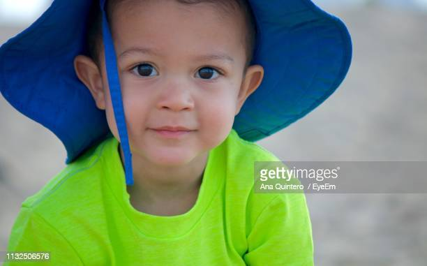 Close-Up Portrait Of Cute Boy Wearing Hat Outdoors