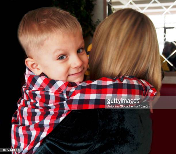 Close-Up Portrait Of Cute Boy With Mother At Home