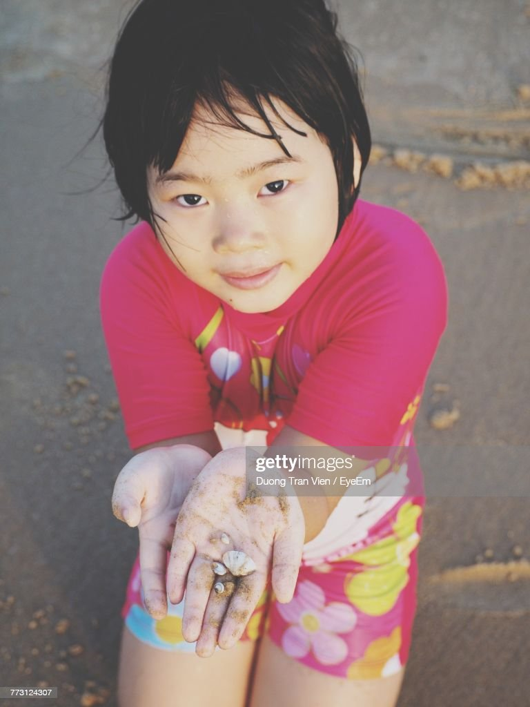 Close-Up Portrait Of Cute Girl At Beach : Photo