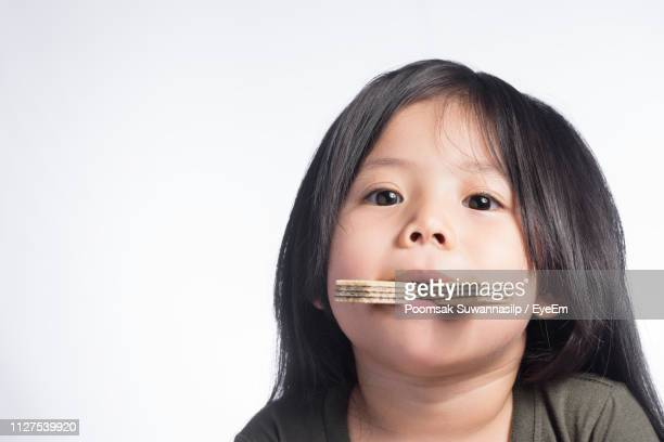 close-up portrait of cute girl eating sweet food against white background - one girl only stock pictures, royalty-free photos & images