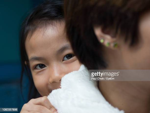 close-up portrait of cute girl hiding behind mother - vietnamese culture stock pictures, royalty-free photos & images