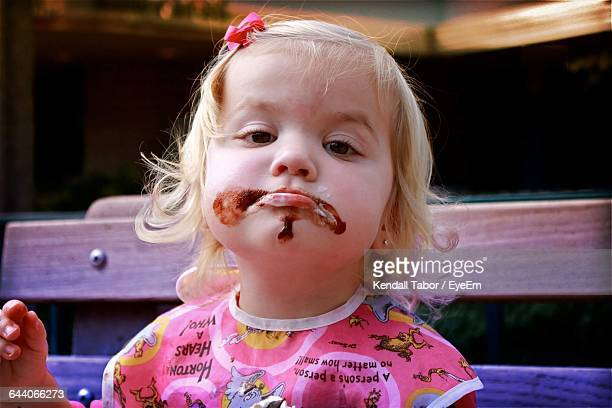 Close-Up Portrait Of Cute Girl With Chocolate On Face