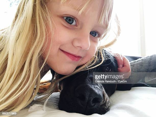 Close-Up Portrait Of Cute Girl With Dog On Bed