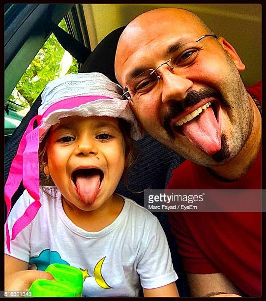 Close-up Portrait Of Father And Daughter Sticking Out Tongue