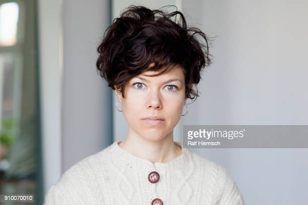 close-up portrait of frowning woman with short hair against wall - green eyes stock pictures, royalty-free photos & images