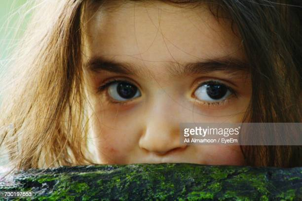 Close-Up Portrait Of Girl Behind Moss Covered Rock