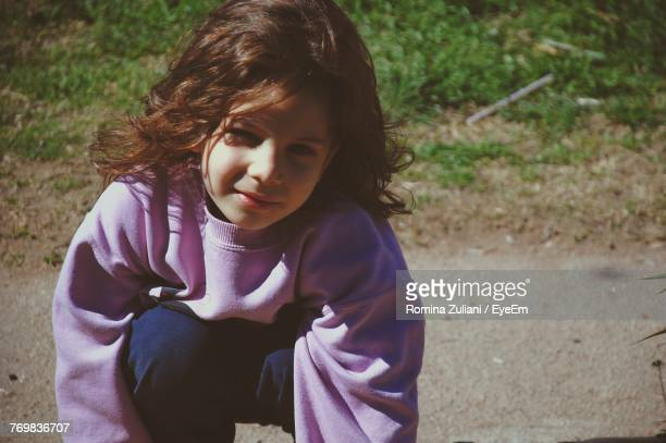Close-Up Portrait Of Girl Crouching On Road
