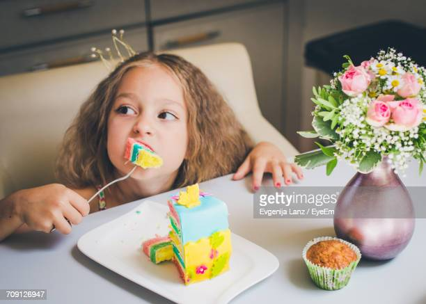 close-up portrait of girl eating cake - happybirthdaycrown stock pictures, royalty-free photos & images