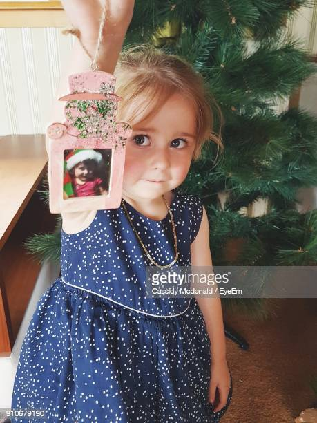 Close-Up Portrait Of Girl Holding Picture Frame While Standing By Christmas Tree