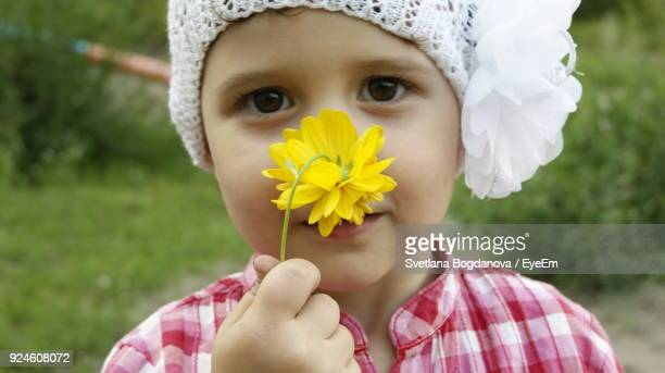 Close-Up Portrait Of Girl Holding Yellow Flower