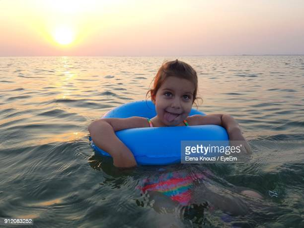 close-up portrait of girl in sea during sunset - elena knouzi stock pictures, royalty-free photos & images