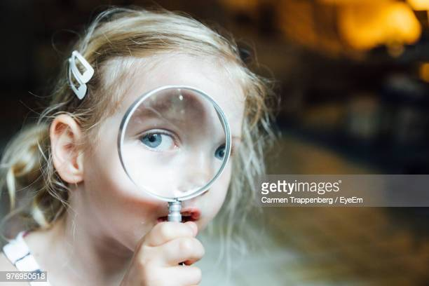 close-up portrait of girl looking through magnifying glass - magnifying glass stock pictures, royalty-free photos & images