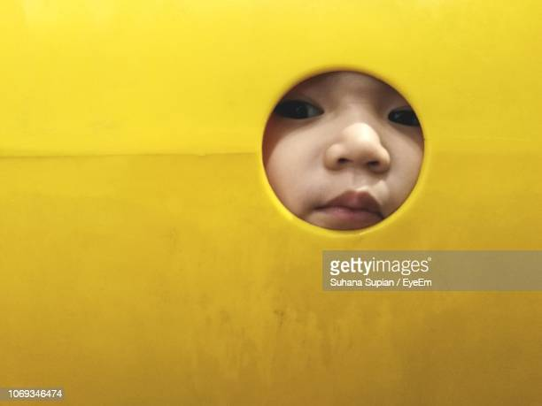 close-up portrait of girl peeking through hole - peeping holes ストックフォトと画像