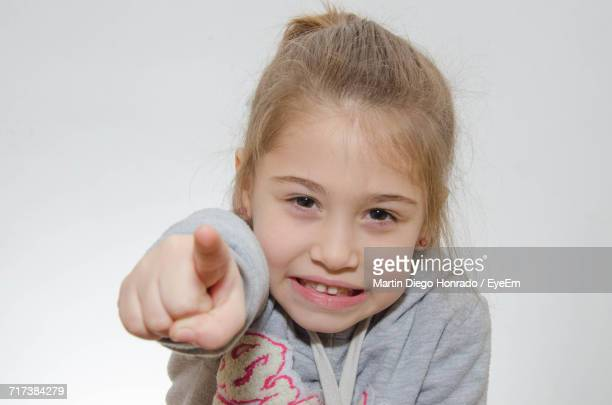 Close-Up Portrait Of Girl Pointing Against White Background