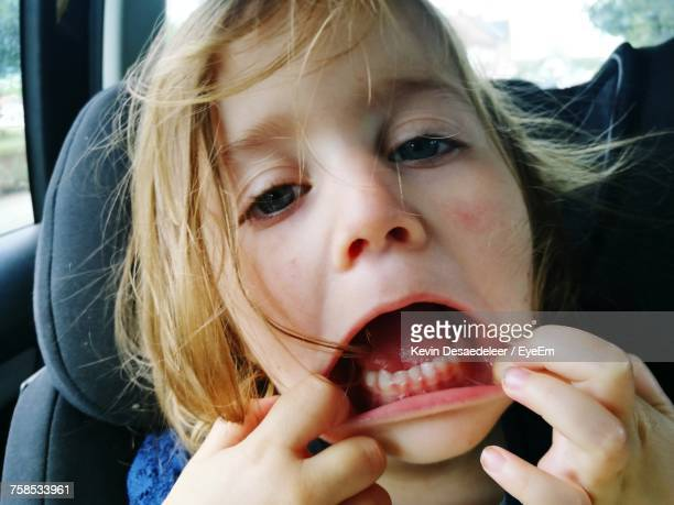 Close-Up Portrait Of Girl Stretching Mouth While Traveling In Car
