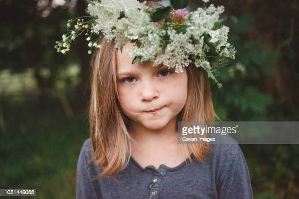 Close-up portrait of girl wearing flowers while standing at farm