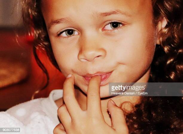 Close-Up Portrait Of Girl With Finger In Mouth