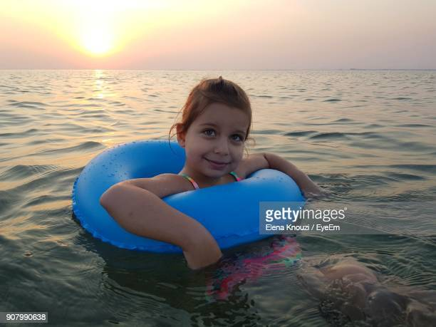 close-up portrait of girl with inflatable ring in sea during sunset - elena knouzi stock pictures, royalty-free photos & images