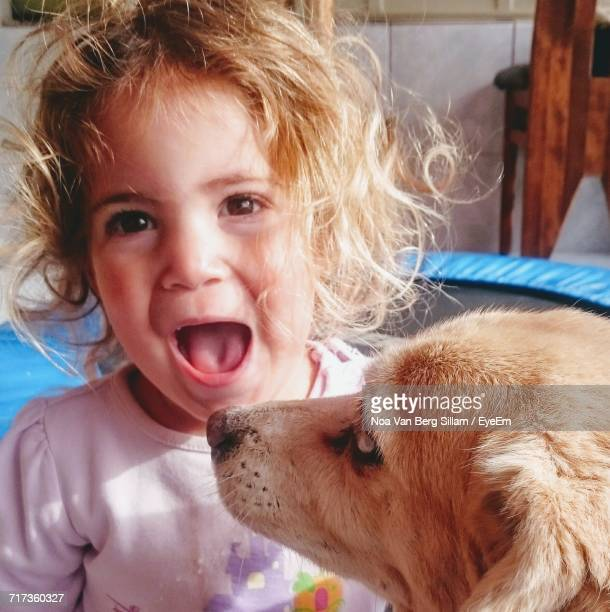 close-up portrait of girl with mouth open by dog at home - girls open mouth stock photos and pictures