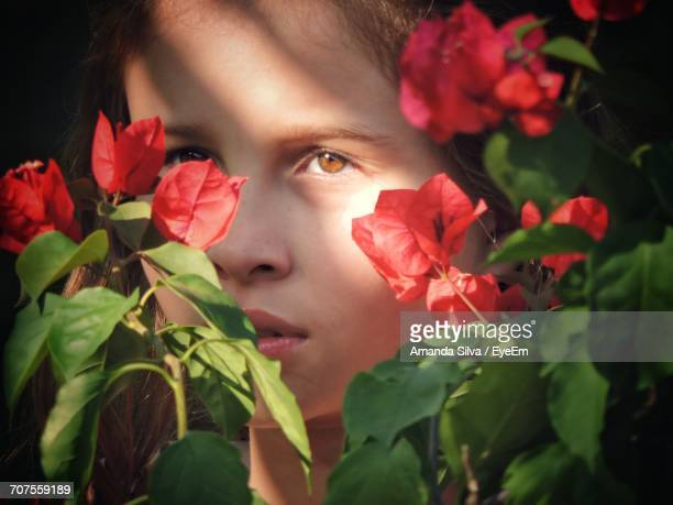 Close-Up Portrait Of Girl With Red Flowers