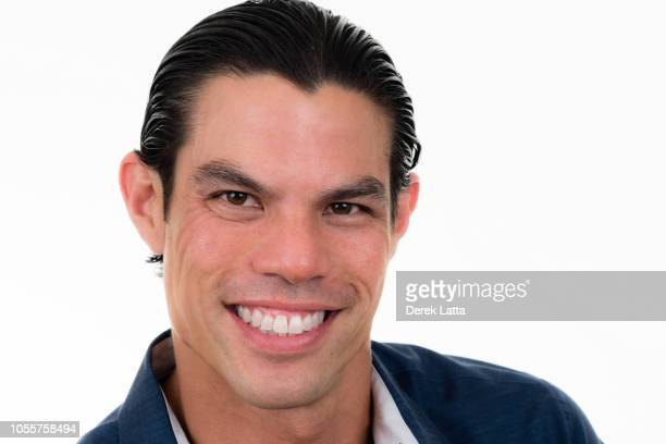 Close-up portrait of handsome confident Asian American man in his 30s smiling'n