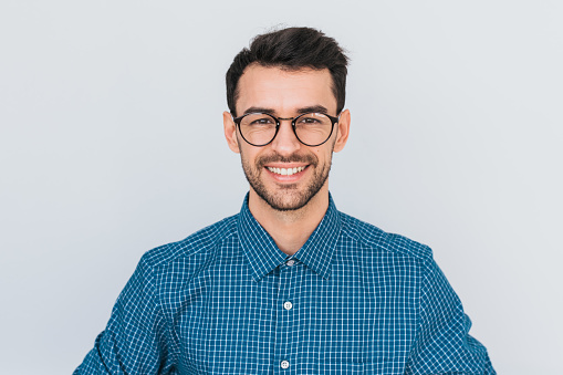 Closeup portrait of handsome smart-looking smiling with toothy smile male posing for social advertisement, isolated on white background with copy space for your promotional information or content. 951331990