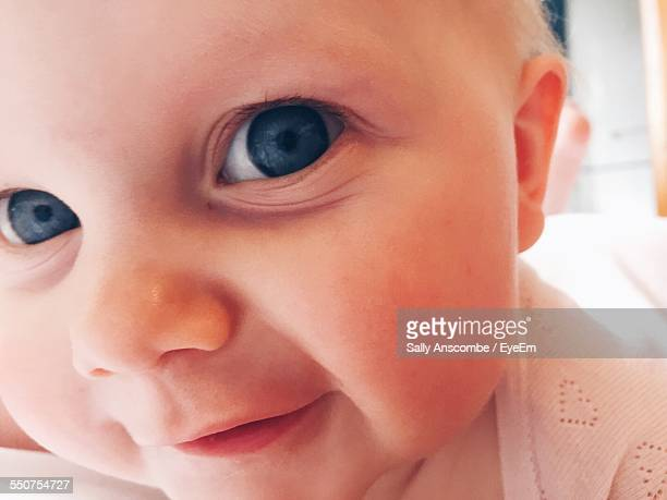 Close-Up Portrait Of Happy Baby Girl On Bed