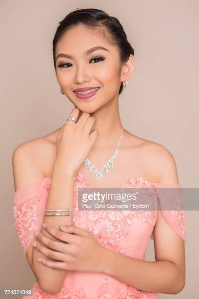 close-up portrait of happy beautiful woman wearing peach dress against beige background - hand on chin stock pictures, royalty-free photos & images