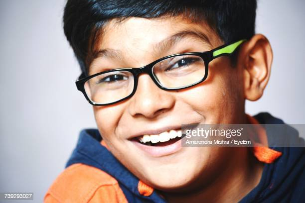 Close-Up Portrait Of Happy Boy Wearing Eyeglasses Against Wall