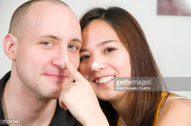 Close-Up Portrait Of Happy Couple With Cream On Nose