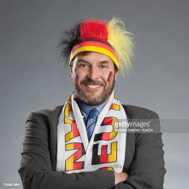 Close-Up Portrait Of Happy German Soccer Fan In Suit Standing Against Gray Background