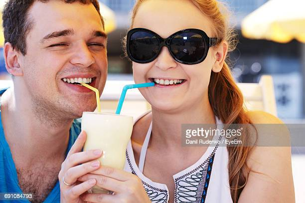 Close-Up Portrait Of Happy Man And Woman Drinking Cocktail