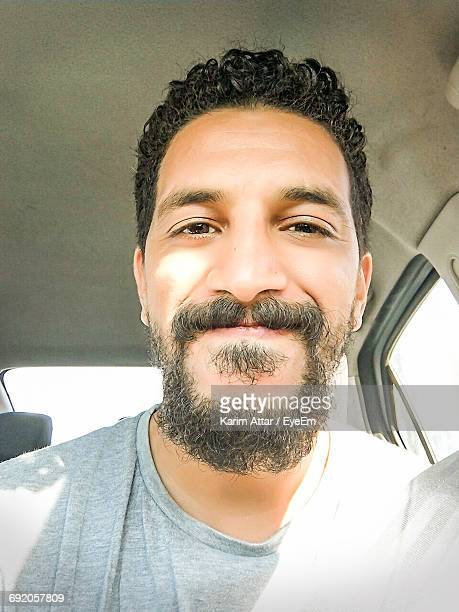 Close-Up Portrait Of Happy Man Sitting In Car