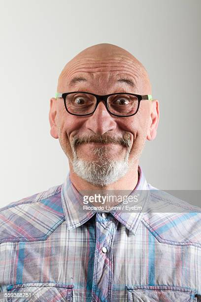 Close-Up Portrait Of Happy Mature Man Making Face Against Gray Background
