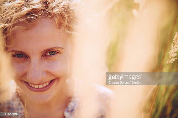close-up portrait of happy young woman seen through grass - bortes cristian stock photos and pictures
