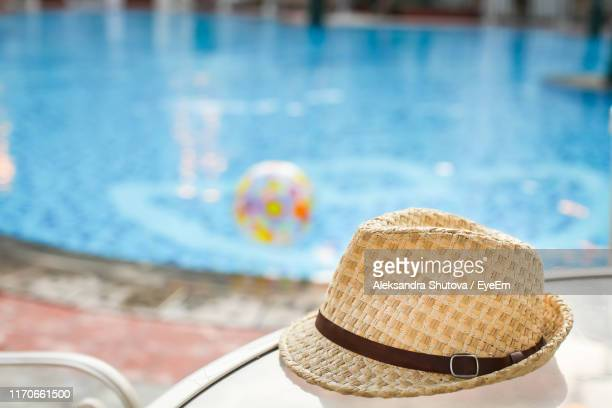 close-up portrait of hat on table by swimming pool - poolside stock pictures, royalty-free photos & images