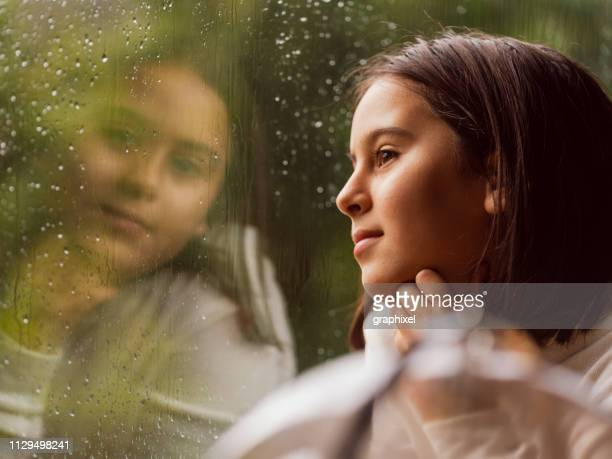 close-up portrait of little girl next to rainy window - speranza foto e immagini stock
