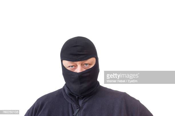 close-up portrait of male burglar wearing balaclava against white background - thief stock pictures, royalty-free photos & images