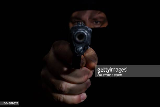close-up portrait of male thief aiming gun against black background - terrorism stock pictures, royalty-free photos & images