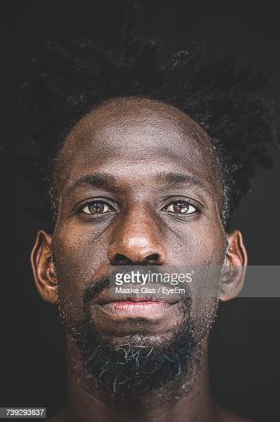 Close-Up Portrait Of Man Against Black Background