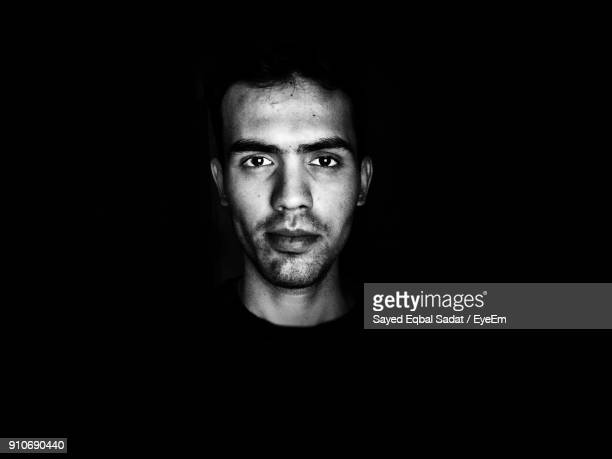 close-up portrait of man against black background - black and white face stock photos and pictures