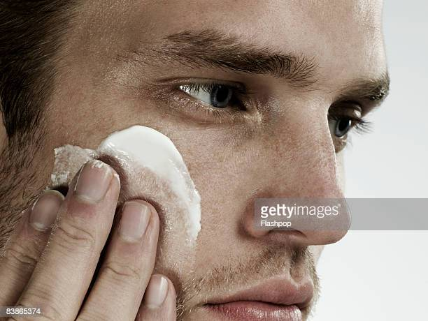 Close-up portrait of man applying moisturizer