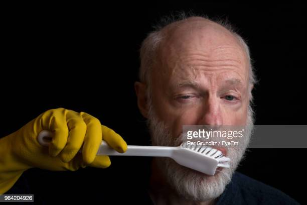Close-Up Portrait Of Man Brushing Teeth Over Black Background