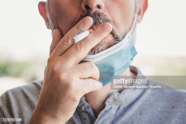 close-up portrait of man holding hands - smoking issues stock pictures, royalty-free photos & images