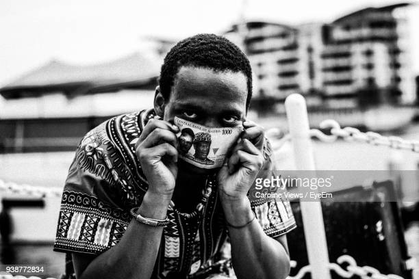close-up portrait of man holding paper currency - nigeria money stock photos and pictures